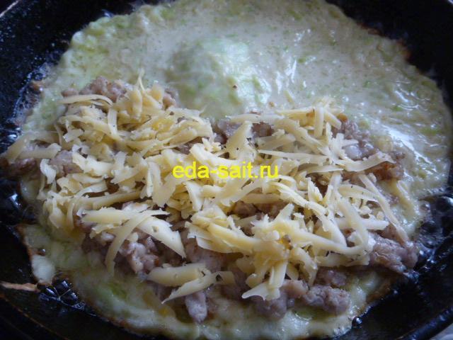 Посыпаем сыром лепешки из кабачков с фаршем