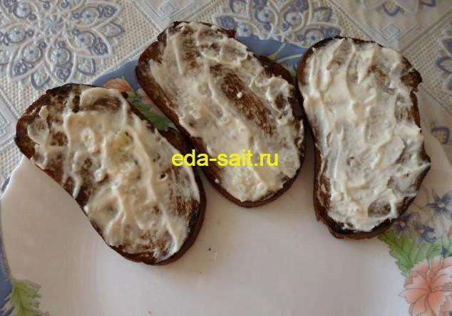 Смазать обжаренный ржаной хлеб майонезом с чесноком