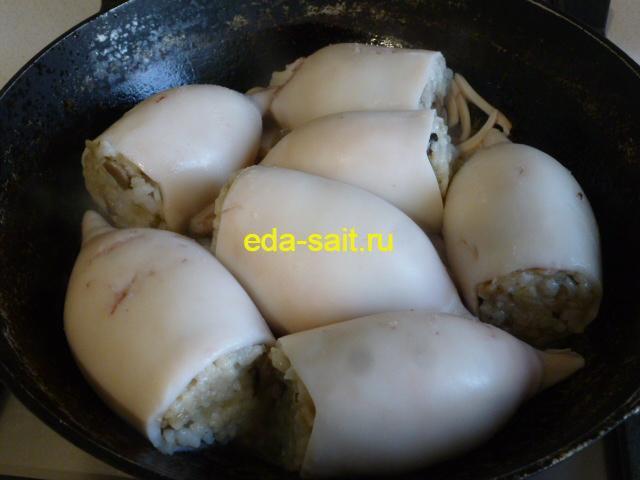 Выложить кальмары фаршированные рисом и грибами в сковороду
